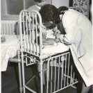 Photo:Nurse and doctor examining an infant, 1970 (catalogue reference: SBHF/PG/28)