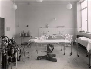 Photo:An operating theatre equipped with an operating table, an anaesthetic machine, instrument tables, prepared sterile drums and a trolley, 1951 (Catalogue reference: SBHH-PG-49).